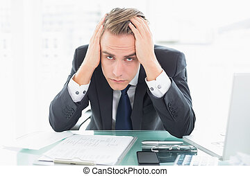 Worried businessman sitting at office desk - Portrait of a...