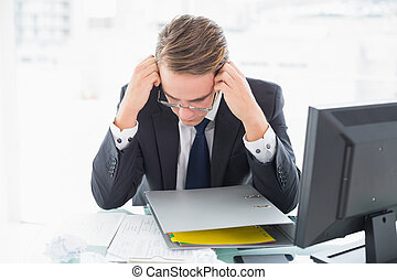 Concentrated businessman reading document at office desk -...
