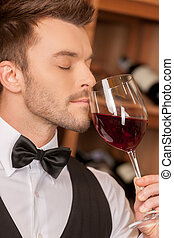 Confident sommelier. Side view of confident young sommelier holding a wine glass and keeping his eyes closed