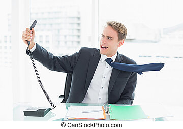 Businessman shouting as he holds out phone at office -...