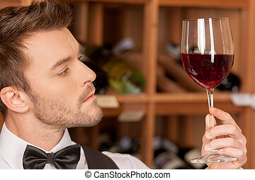 Confident sommelier. Side view of confident young sommelier holding a wine glass and examining it