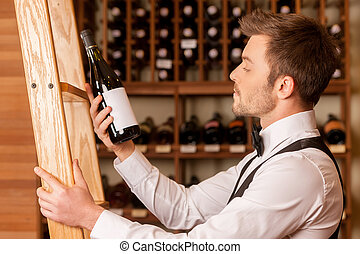 Confident sommelier. Side view of thoughtful young sommelier holding a wine bottle and examining it