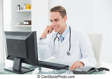 Doctor using computer at medical of - Smiling young male...