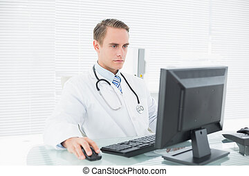 Doctor using computer at medical office - Serious male...