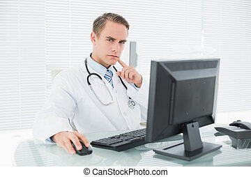Serious doctor using computer at medical office - Portrait...