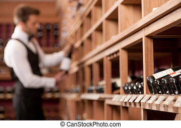Confident sommelier Thoughtful young sommelier holding a...