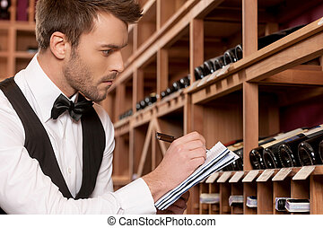 Confident sommelier. Side view of confident young sommelier...