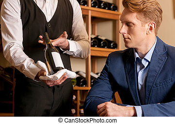 Sommelier and customer. Sommelier showing a wine bottle to...