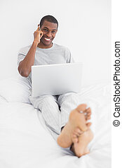 Afro young man using cellphone and laptop in bed - Portrait...