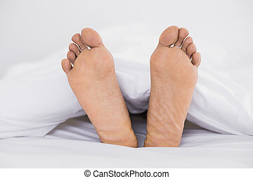 Close up of bare feet in bed at home