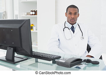 Serious male doctor with computer at medical office