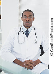 Serious male doctor sitting at medi - Portrait of a...