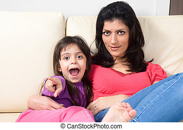 Mother and daughter lying on the couch