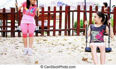 Girls swinging in summer playground