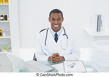 Smiling doctor with laptop at medical office - Portrait of a...