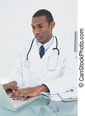 Doctor using laptop at medical office - Concentrated male...