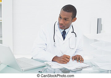 Doctor writing a note while using computer at medical office...