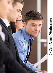 Handsome businessman is looking an smiling. Blur foreground. Sitting in the office