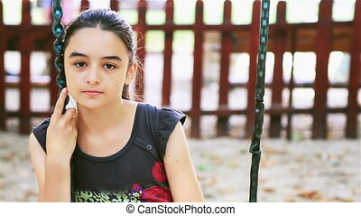 Sad preteen girl sitting on swing in playground