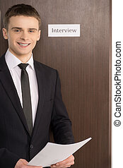 Confident man is standing with CV Door with interview tablet...