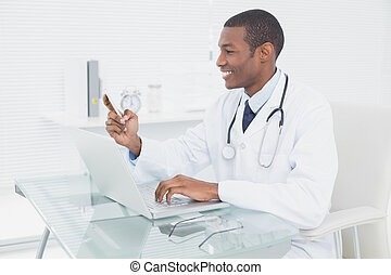 Smiling male doctor text messaging while using laptop - Side...