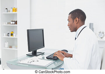 Concentrated doctor using computer at medical office - Side...