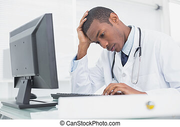 Worried male doctor using computer at medical office