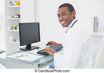 Smiling doctor using computer at medical office - Side view...