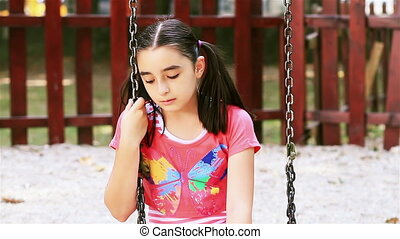 Sad young girl sits on swing in summer park
