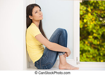 Girl at home. Beautiful young woman sitting on the windowsill and looking away