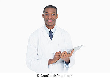 Portrait of a smiling male doctor with clipboard against...
