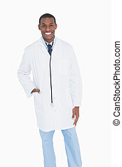 Portrait of a happy male doctor standing against white...