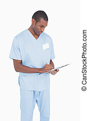 Serious male surgeon writing on clipboard against white...