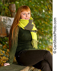 Beautiful long red haired woman in the autumn park