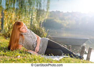 Beautiful-haired woman relaxing on the shore of Lake