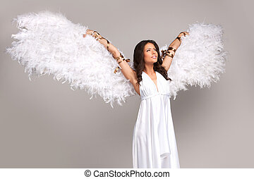 Girl with wings. Beautiful young woman with white wings looking away while standing isolated on grey