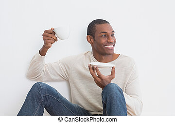 Casual Afro man having tea against wall - Casual happy Afro...