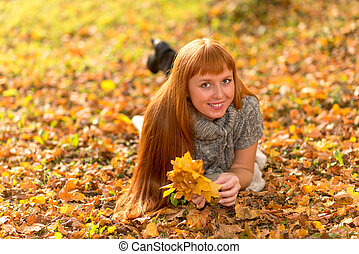 Woman in the autumn leaves