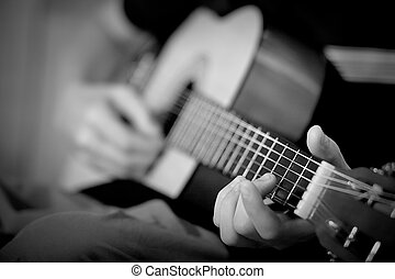 Strumming - A person plays a guitar with just a part of neck...