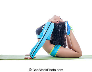 Curly flexible brunette doing gymnastic ring on mat