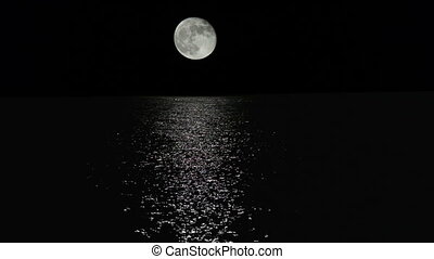 Moonlight path with low fool moon above the sea