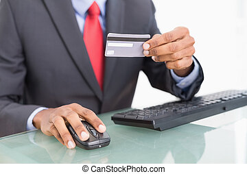 Close up mid section of a businessman doing online shopping...