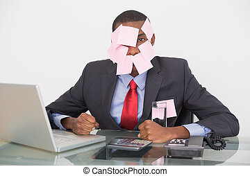 Afro businessman with blank notes on face and laptop -...