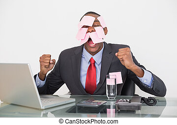 Frustrated Afro businessman with blank notes on face and...