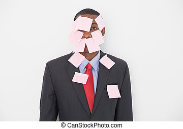 Portrait of an Afro businessman covered in blank notes over...