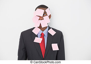 Young Afro businessman covered in blank notes over white...