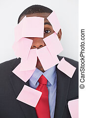 Close up portrait of Afro businessman covered in blank notes...