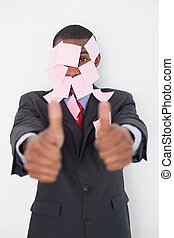 Afro businessman covered in blank notes gesturing thumbs up...