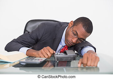 Afro businessman resting at desk ov - Young Afro businessman...
