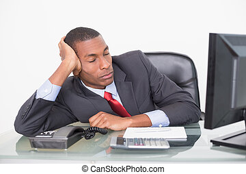 Young Afro businessman resting at desk against white...